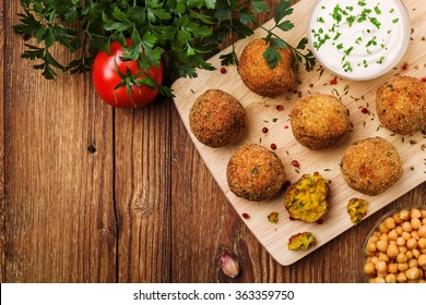 Chickpea falafel balls on a wooden desk with vegetables