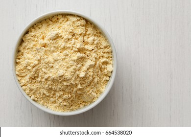 Chickpea flour in white ceramic bowl isolated on painted white wood from above.