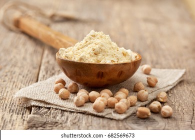 Chickpea flour in a wooden spoon, chickpeas on old wooden background