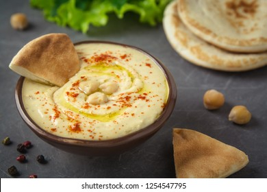 Chickpea hummus in a bowl and pita bread on grey background. Mediterranean snack, vegetarian healthy food concept. Top view, flat lay, copy space.