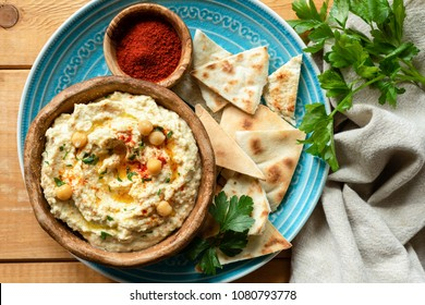 Chickpea hummus, pita chips, paprika and parsley. Top view
