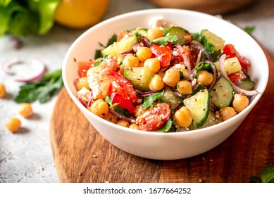 Chickpea salad with tomatoes, cucumber, feta cheese, parsley, onions and lemon in a plate on a served table, selective focus. Tasty and healthy vegetarian food, oriental and Mediterranean cuisine.