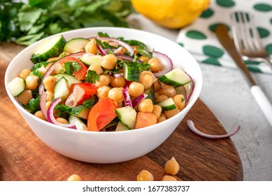 Chickpea salad with tomatoes, cucumber, parsley, onions, olive oil and lemon in a bowl on a served table. Tasty and healthy vegan food.