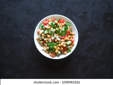 Chickpea salad with vegetables on a black background. Summer vegetarian diet.