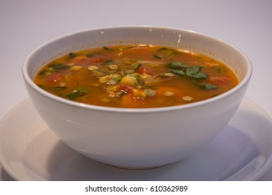 Chickpea soup with cheese, parsley, tomato, peas and carrot - healthy organic vegetarian meal