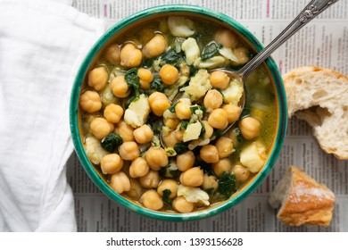 Chickpea soup with spinach and dry salted cod in a rustic bowl on a newspaper background