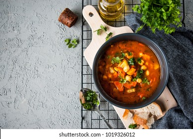 Chickpea soup, vegan. Served in a bowl, on a wooden board with bread, oil and parsley. Gray, structural background. Flat lay food.