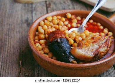 Chickpeas, sausage and bacon in a crockpot by a little metal spoon. Typical food from Madrid, Spain, with a rustic wooden board as a background.
