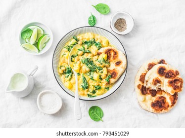 Chickpeas, spinach, potato curry plate and naan flatbread on white background, top view. Indian healthy vegetarian food