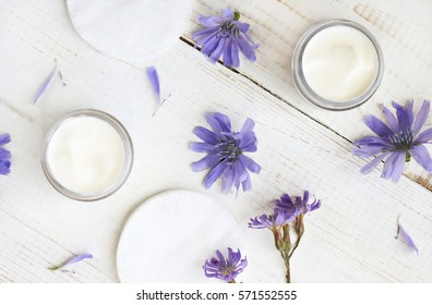 Chicory infused facial cream. Blue flowers and sample products over white table. Herbal cosmetics