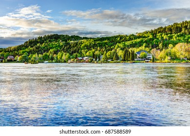 Chicoutimi river in Saguenay, Quebec, Canada with riverfront houses and forest during sunset