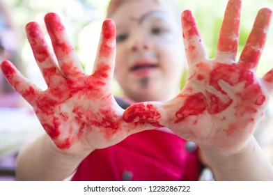 Chid boy showing his red stained hands after arts workshop for children. Closeup