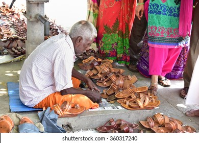 CHIDAMBARAM, TAMIL NADU, INDIA, SEPTEMBER 23, 2015: A cobbler repairing slippers of pilgrims by the roadside near the Thillai Nataraja Temple of Lord Shiva, in the morning.