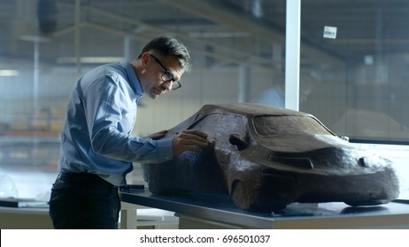 Chief Automotive Designer with Rake Sculpts Futuristic  Car Model from Plasticine Clay. He Works in a Special Studio Located In a Large Car Factory.