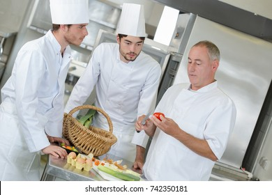 chief chef watching his assistants garnishing a dish