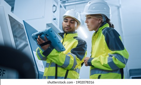 Chief Engineer and Project Manager Wearing Safety Vests and Hard Hats, Use Digital Tablet Controller in Modern Factory, Talking, Programming Machine For Productivity. Low Angle Portraits