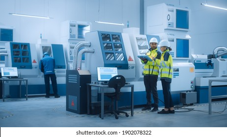 Chief Engineer and Project Manager Wearing Safety Vests and Hard Hats, Use Digital Tablet Controller in Factory, Optimizing CNC Machinery Programming Machine for Increasing Production Line Efficiency
