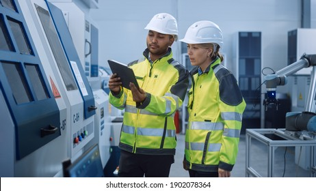Chief Engineer and Project Manager Wearing Safety Vests and Hard Hats, Use Digital Tablet Computer in Modern Factory, Talking, Optimizing CNC Machinery, Programming Machine for Increasing Efficiency