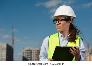 Chief Engineer Woman In Green Vest And Helmet Standing Outside On A Sunny Summer Day. Reconstruction Concept
