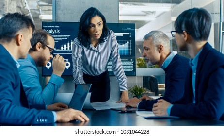 Chief Female Executive Leans and Spreads Project Blueprints on the Table Showing them to Her Colleagues. In the Background Pie Charts and Company's Growth on the Wall TV.