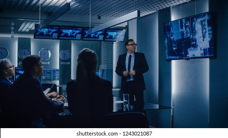 Chief of Operations Shows Surveillance Footage on Wall TV Screen to a Team of Government Special Agents. System Control Monitoring Room