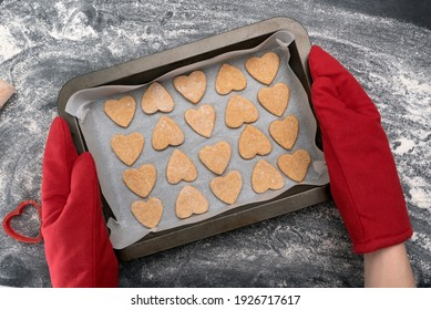 Chief in oven mitts holding freshly baked heart-shaped cookies