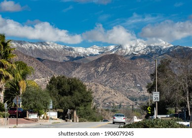 Chiefs Peak Mountain over Ojai, California is covered in snow and low clouds while overlooking highway 33 traveled by cars.