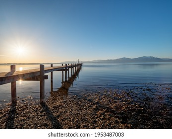 Chiemsee footbridge view during sunrise phase with alp mountain chain at the background