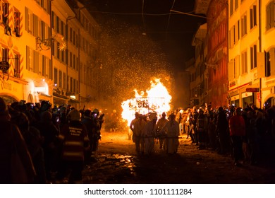 Chienbaese festival. Switzerland, Liestal, Rathausstrasse 25, 18th of February 2018. Festival participants pulling a wagon stacked with burning wood through the old town.