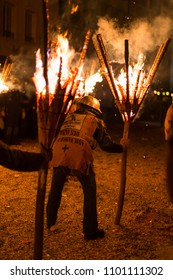 Chienbaese festival. Switzerland, Liestal, Rathausstrasse 25, 18th of February 2018. Festival participants carrying burning broom shaped wooden logs on their shoulders through the old town.
