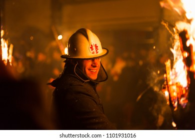 Chienbaese festival. Switzerland, Liestal, Rathausstrasse 25, 18th of February 2018. Close-up of a festival participant carrying burning broom shaped wooden logs through the old town.