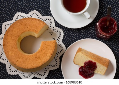 Chiffon cake with characteristic hole in the center from an ungreased tube pan. The cake is made with vegetable oil, eggs, sugar, flour, and flavorings. Served with raspberry jam, and a cup of tea.