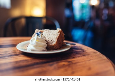 chiffon cake with cream and cafe on wooden background