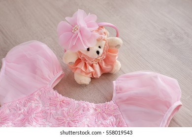 Chiffon dress and hoop hair. Gentle pink dress of chiffon on a wooden table. Hoop hair put on a teddy bear as a girl. On dress beaded embroidery. Clothing for girls pink. Children's clothing.