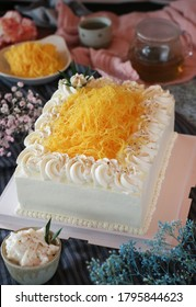 A chiffon sponge pound cake with whipped cream fusion with Thai traditional golden egg yolk threads(Foi Thong) and sweet coconut cream with tea on a table decorated with variety of flowers