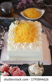 A chiffon sponge pound cake with whipped mascarpone cream fusion with Thai traditional golden egg yolk threads(Foi Thong) and sweet coconut cream with tea on a table