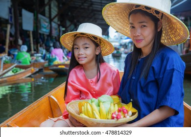 Chikd and mother sit on the boat and hold the fruit basket in Traditional floating market ,bangkok,  Thailand.