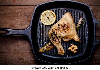 Chiken and vegetables on grill pan on old wooden table or board. Toned.