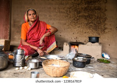 CHIKHALDARA, MAHARASHTRA - AUGUST 28, 2018: An Unidentified old woman making and cooking / baking fresh food in a rural village in a vintage kitchen using firewood in earthen chulhas.