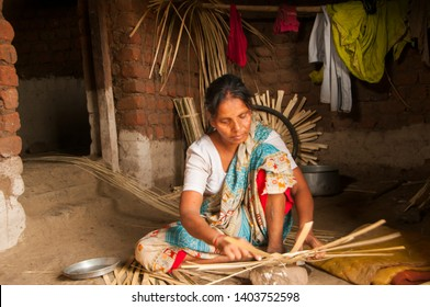 CHIKHALDARA, MAHARASHTRA, INDIA 6 NOVEMBER 2017 : Unidentified rural woman making basket from bamboo at her home for selling in traditional handicraft bazaar,  An Indian rural scene.