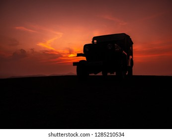 Chikmagalur, India- December 21, 2018 : off road SUV in silhouette standing on a mountain peak around sunset