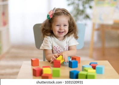 child 2 years ago playing wooden toys at home or kindergarten