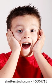 Child 4 to 5 years old, amazed with his hands in his face over white background