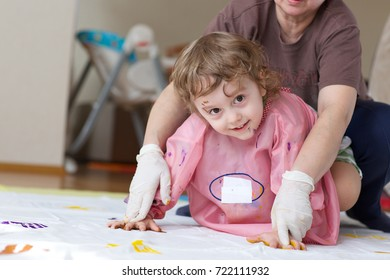 Child of 4 years old is painting white blanket with their palms