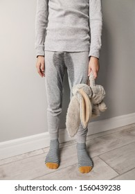child 9 years old, standing in pajamas on a background of a gray wall. psychological and physical health problem. wet pants due to incontinence. the child is experiencing, feeling shame