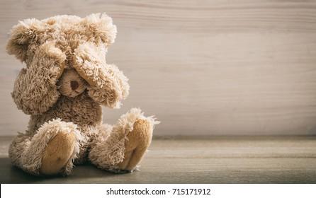 Konzept des Kindesmissbrauchs. Teddybär mit Augen in einem leeren Raum, Draufsicht, Kopienraum
