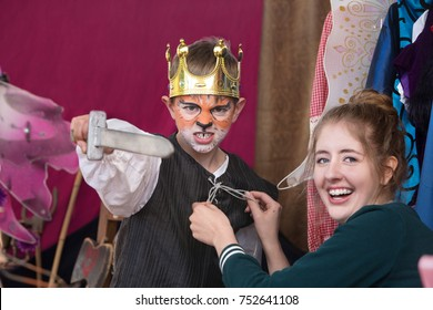 Child actor dressed as king with crown brandishes sword as assistant helps him
