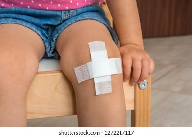 Child with adhesive bandage on knee - injury concept