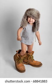 Child in adult's yellow shoes and hat earflaps