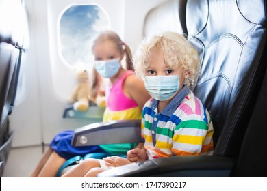 Child in airplane in face mask. Virus outbreak. Coronavirus and flu pandemic. Safe travel with young child and baby. Kids flying airplane in surgical masks.